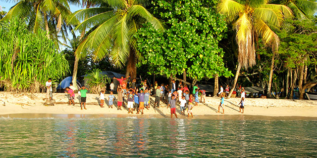 Residents of The Marshall Islands spill onto the beach to welcome the guests and crew of Shenandoah