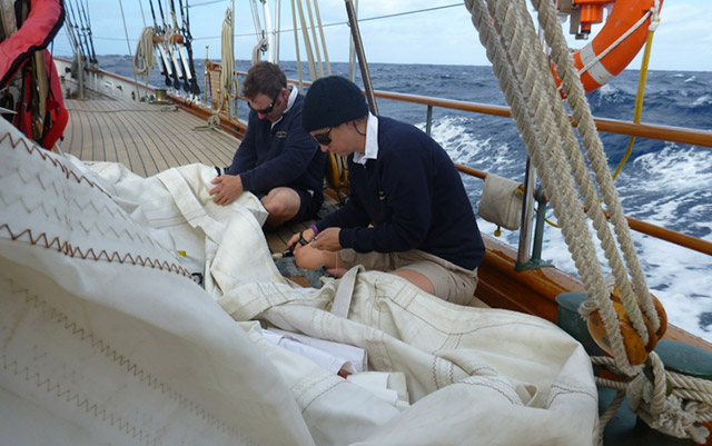 members of the Shenandoah crew hand stitching a torn mizzen sail