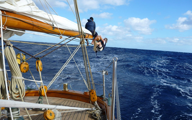 Shenandoah crew members hanging from the end of her mizzen boom
